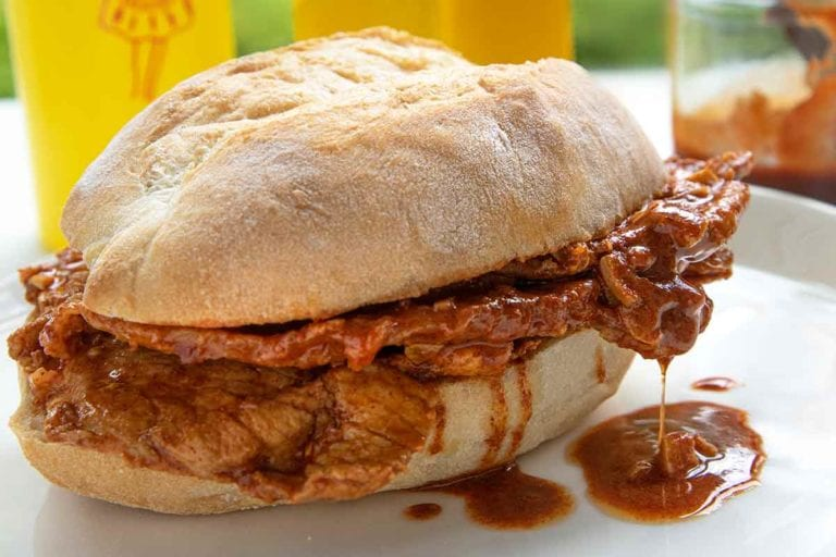 A bifana, a Portuguese pork sandwich on a white plate with a bottle of mustard in the background.