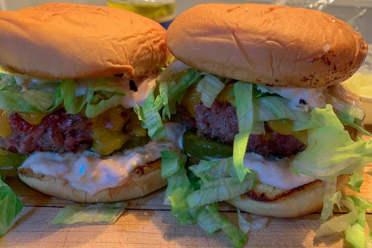 Two pastrami burgers with Russian dressing and iceberg lettuce.