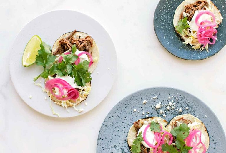 Three plates filled with shredded beef tacos--braised beef brisket, Cotija cheese, napa cabbage, sour cream, red onions, and cilantro on charred corn tortillas