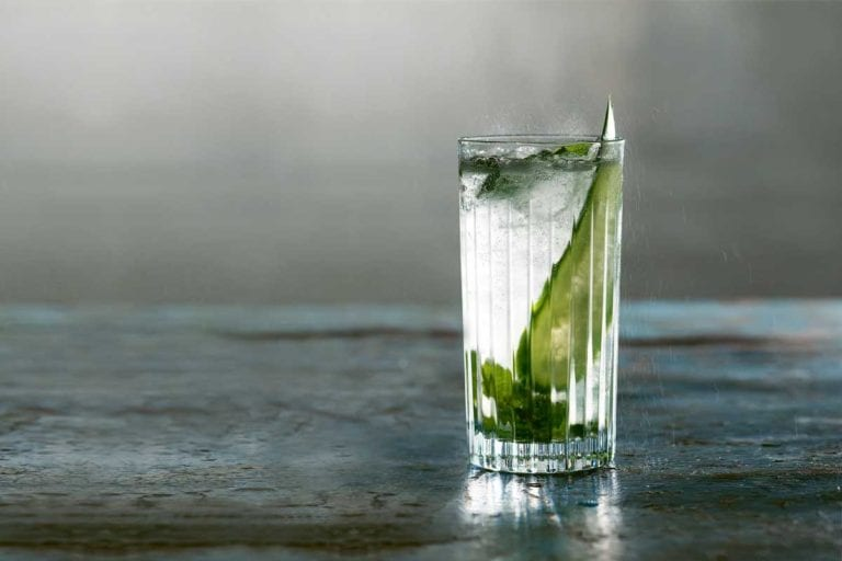 A highball glass filled with British summertime cooler, mint leaves, and a cucumber slice.