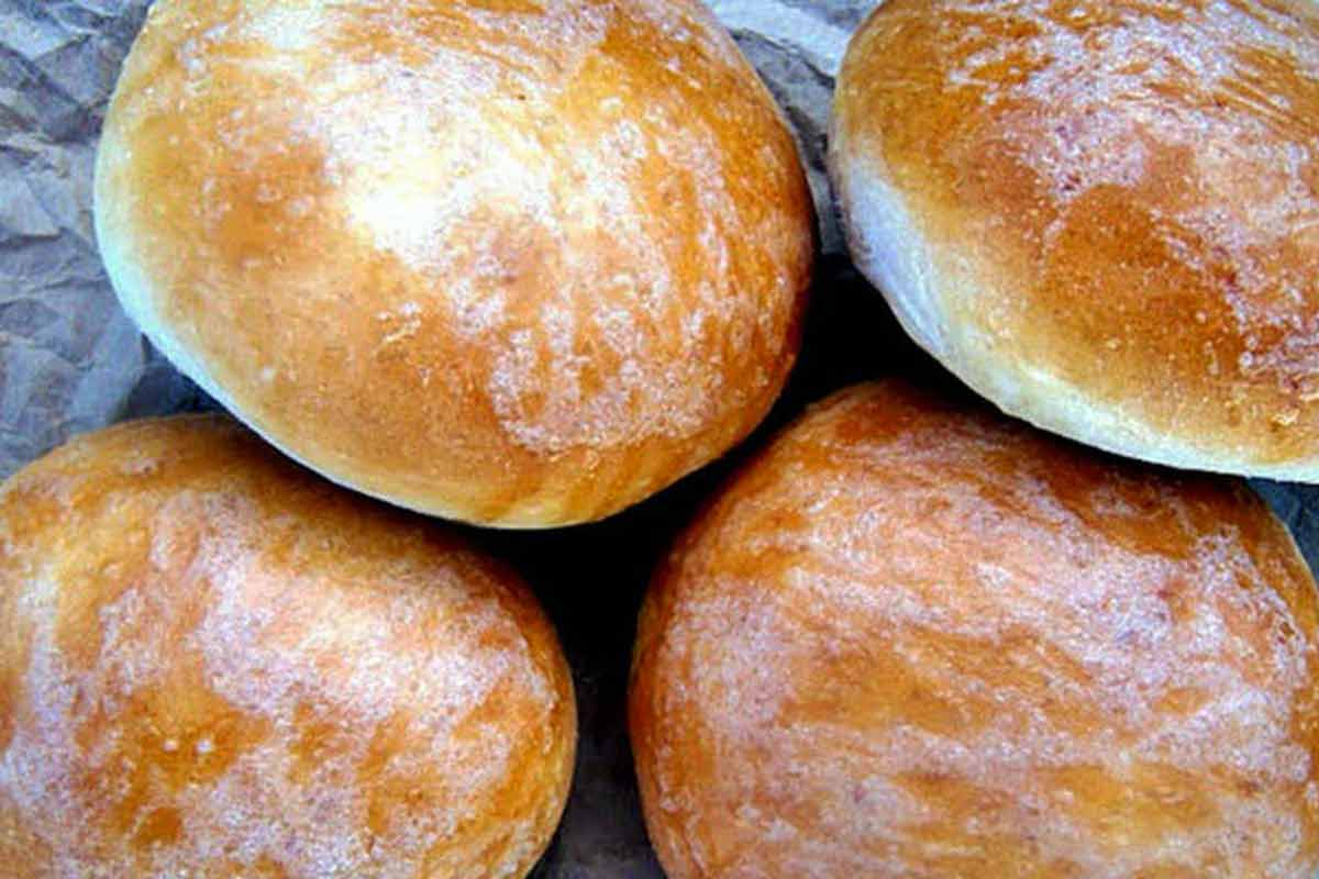 Four homemade burger buns dusted with flour on grey paper.