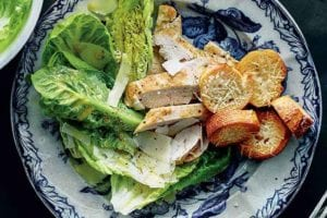 A blue and white plate topped with a deconstructed chicken Caesar salad with baguette round croutons.