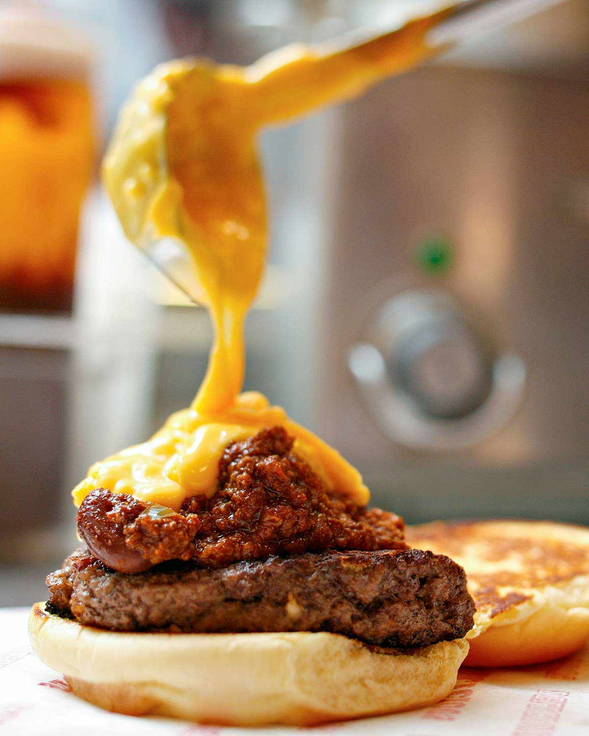 A chili cheddar burger on a bun half with cheese sauce being poured over it.