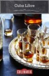 Several shot glasses partially filled with Cuba libre on a silver platter.