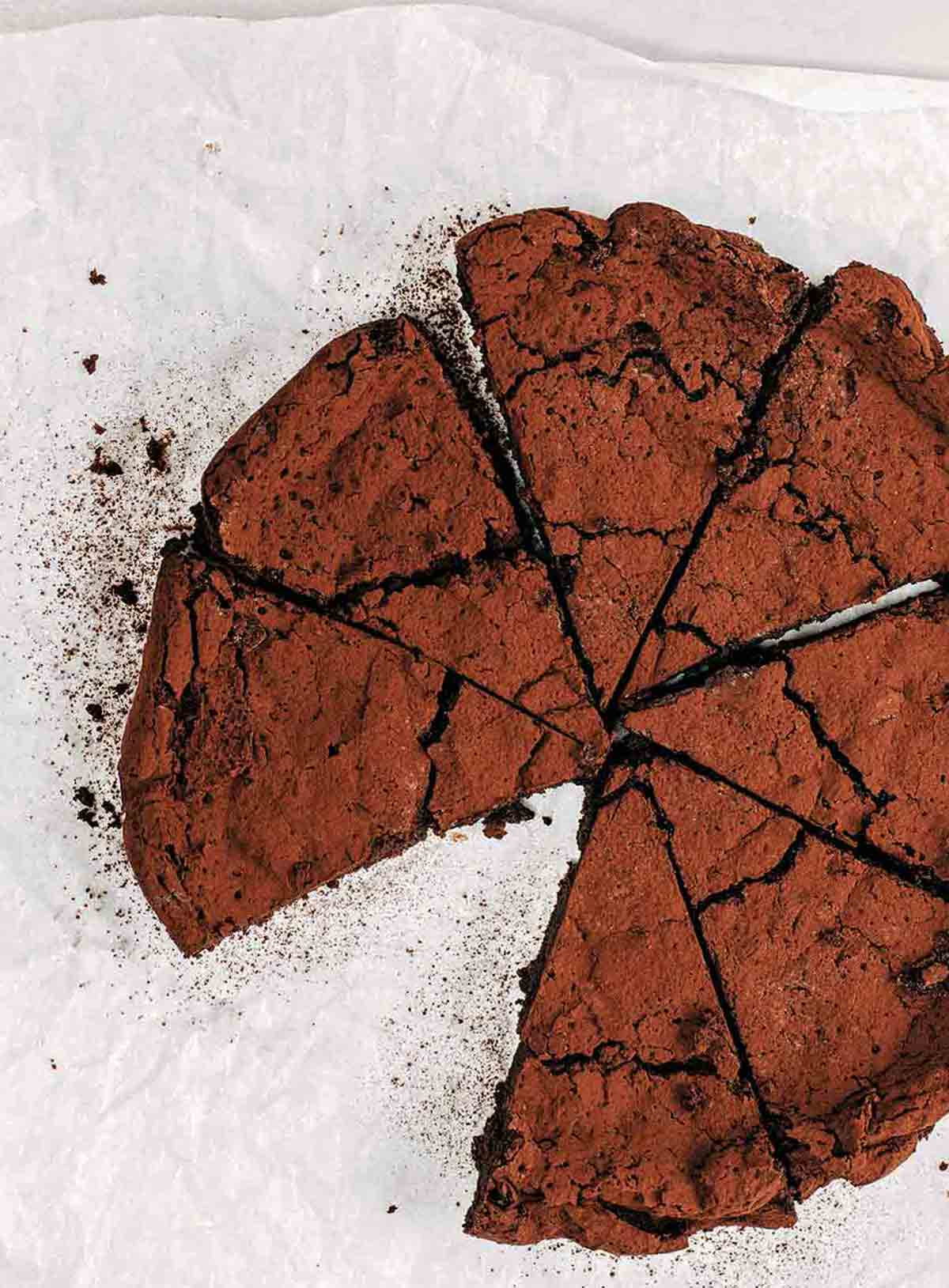 A flourless chocolate chile cake cut into 8 wedges with one slice missing on a piece of parchment paper.