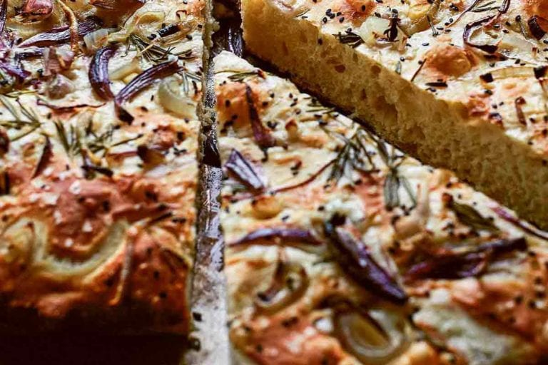A baked loaf of focaccia with red onion and rosemary with two wedges cut from it.