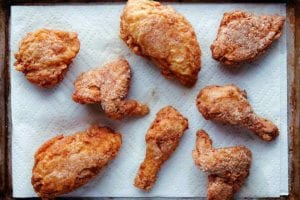 Seven pieces of gluten-free fried chicken on a paper towel-lined rimmed baking sheet.