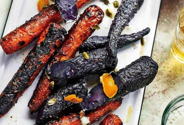 A white enamel platter topped with charred purple and orange grilled carrots.