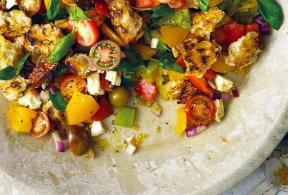 A large bowl filled with grilled panzanella, with cherry tomatoes, torn bread, and basil leaves.