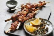 Four grilled pork skewers on a white plate with a bowl of lemon wedges and dried oregano beside the skewers.