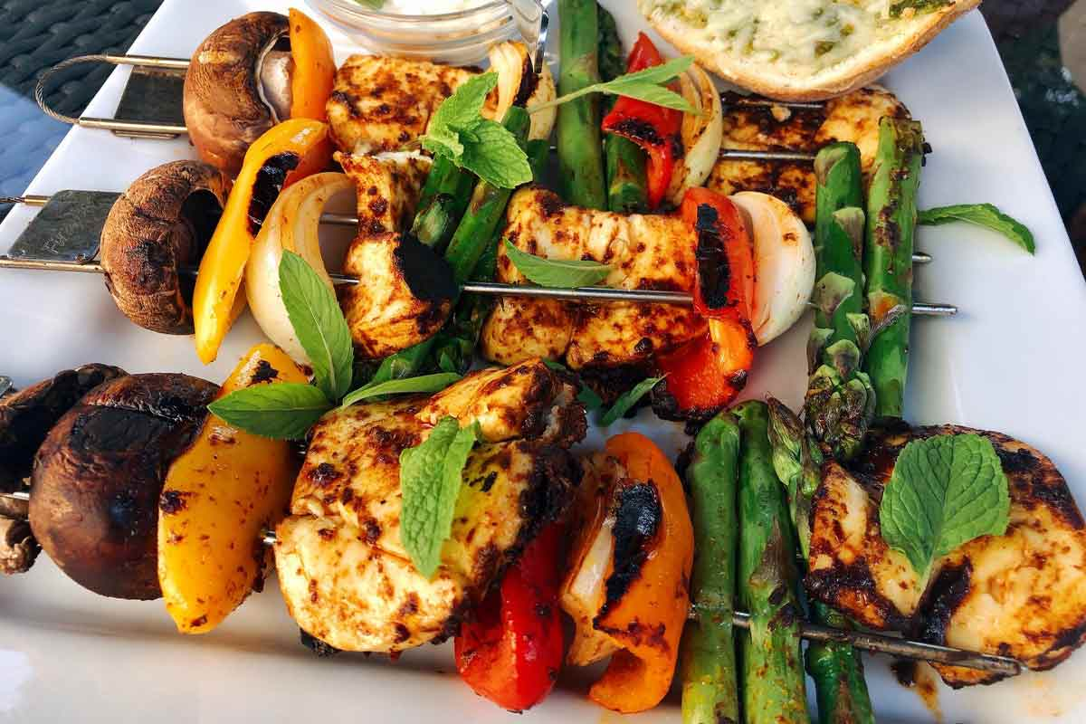 Three harissa vegetable skewers with halloumi on a white plate.