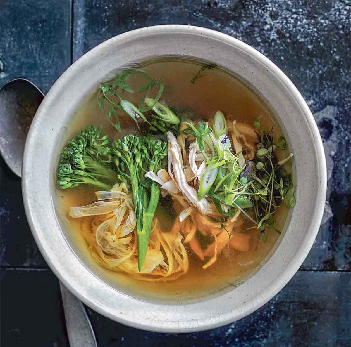 A bowl of healthy egg drop soup with shredded chicken, green onions, broccoli rabe, noodles, and sprouts