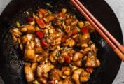 A wok filled with kung pao chicken with two chopsticks on the edge