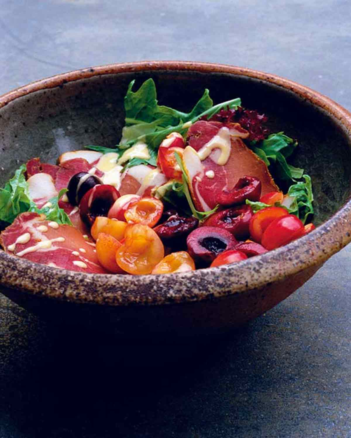 A ceramic bowl filled with mixed green salad with Prosciutto and cherries and drizzled with creamy Dijon dressing.