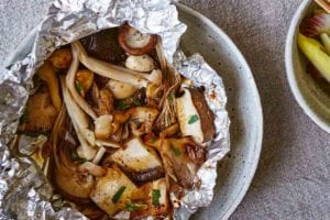 Two pouches of baked mushrooms in foil packets with a bowl of greens and another bowl of quinoa on the side.