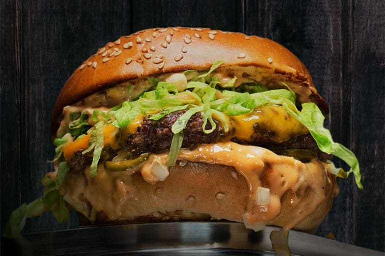 A pastrami burger with Russian dressing and iceberg lettuce.