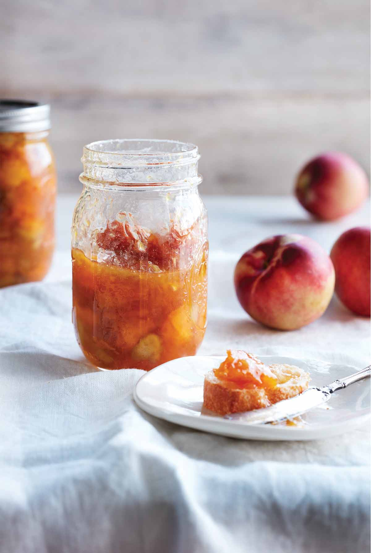 Two jars of peach and rhubarb jam with some peaches in the background and a plate with a piece of bread topped with the jam.