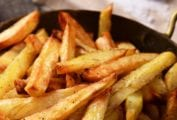A metal bowl with handles filled with seasoned perfect French fries.