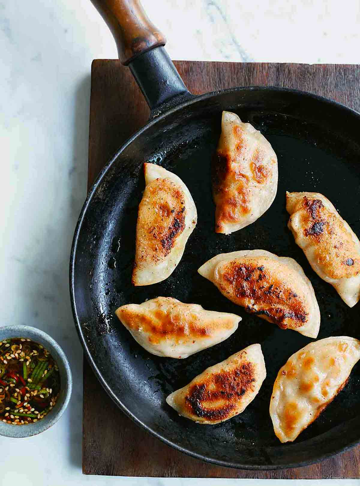 A black skillet with seven pork dumplings in it on a wooden surface and a cup of dipping sauce beside it.
