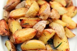 A platter of quartered roasted potatoes on the grill, seasoned with pepper and rosemary.