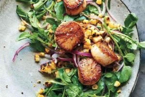 A plate of seared scallops with grilled sweet corn salad, sliced red onion, and watercress.