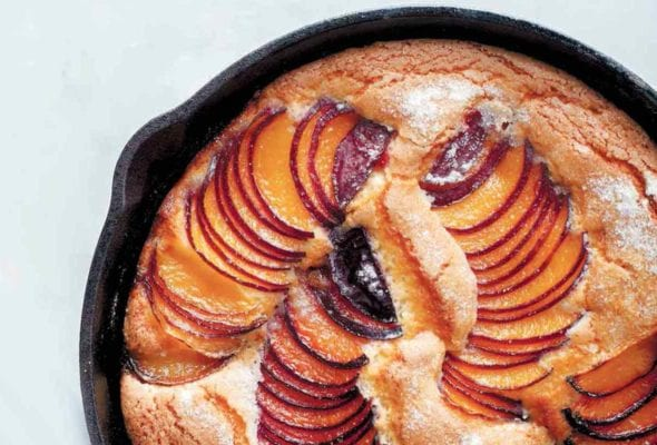 A cast-iron skillet plum cake with slices of fanned out plums baked in