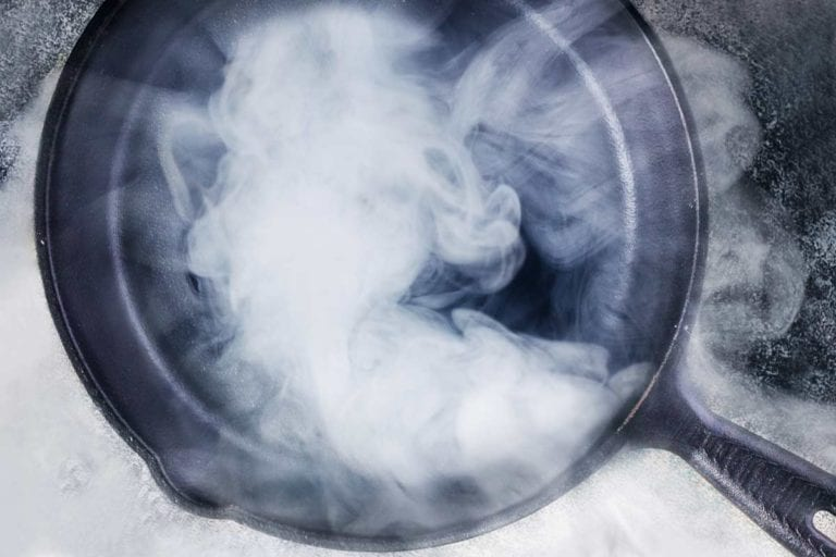 A cast-iron skillet with smoke billowing from an oil that has reached its smoke point.