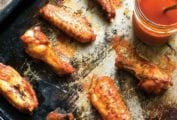 A baking sheet with 6 spicy baked chicken wings glazed with hot sauce, a jar of sauce nearby