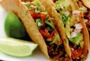 Three sweet and spicy tacos on a white plate with wedges of lime alongside.