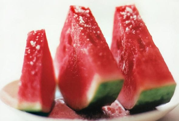 Three slices of watermelon with fleur de sel sprinkled over top.