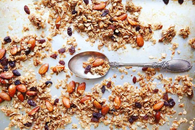 Almond and coconut granola scattered on a baking sheet with a spoon resting in the center.