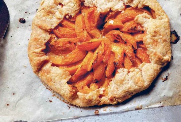 A cooked apricot galette on a piece of parchment paper with a metal spatula beside it.