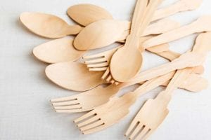 A collection of disposable bamboo utensils in a pile.