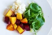 A white plate topped with beet salad with goat cheese and honey and watercress leaves.