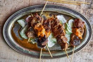 Catalan lamb skewers on sliced cucumbers topped with a romesco sauce
