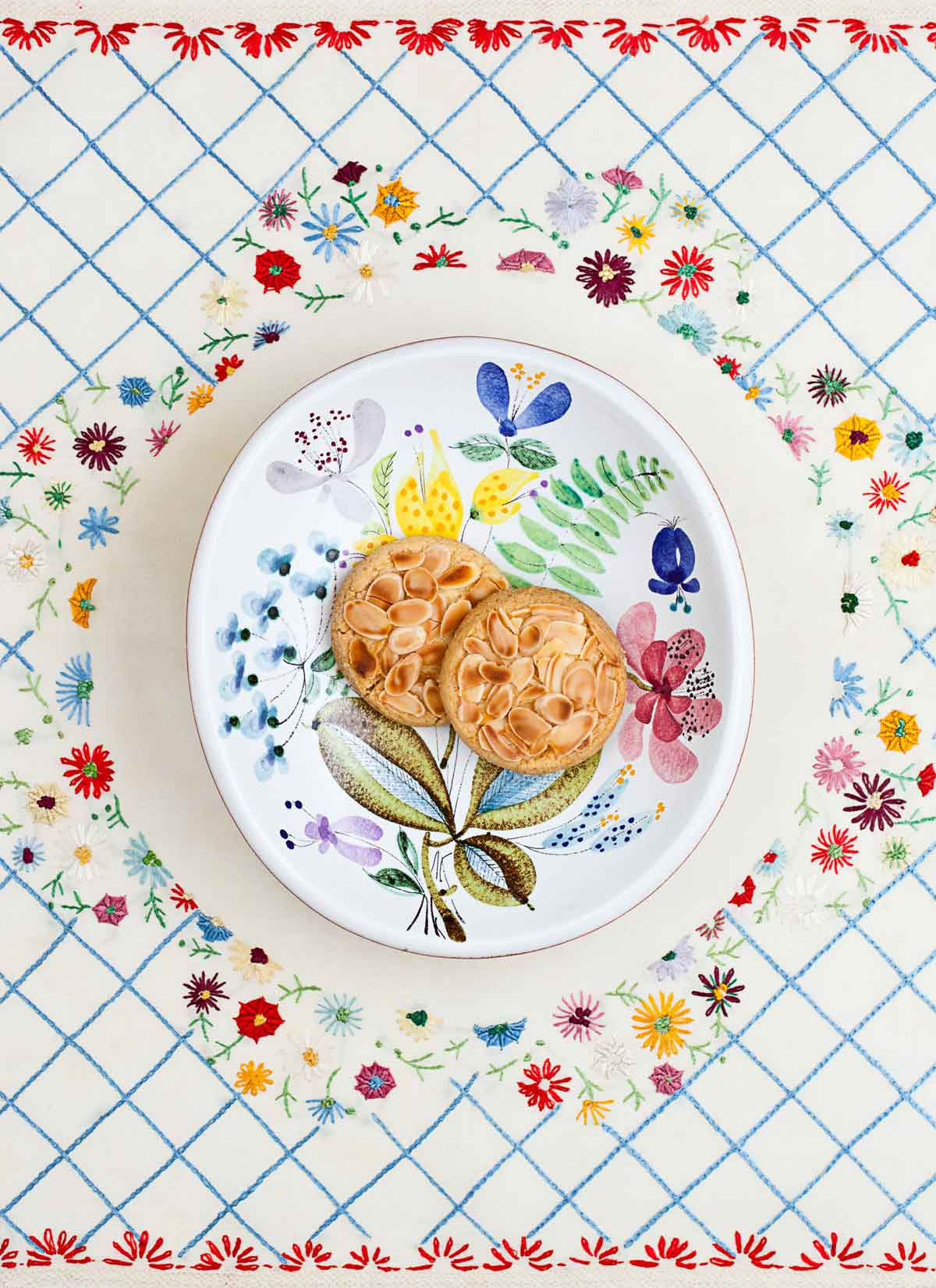 Two almond-topped cookies made by Cenk Sönmezsoy on a decorative plate and cloth.