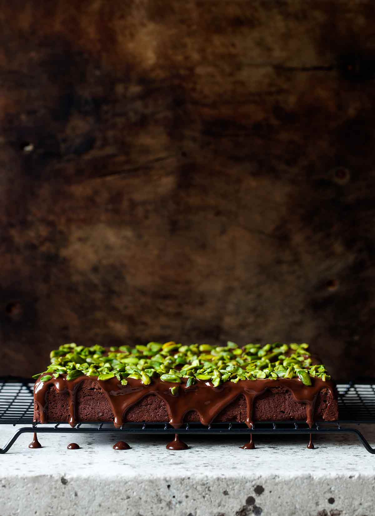 A slab of chocolate brownies with chocolate drizzle and chopped pistachios made by Cenk Sönmezsoy on a wire rack.