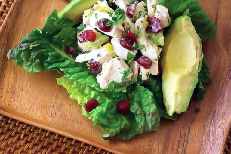 A serving of chicken avocado cranberry salad on a square wooden plate.