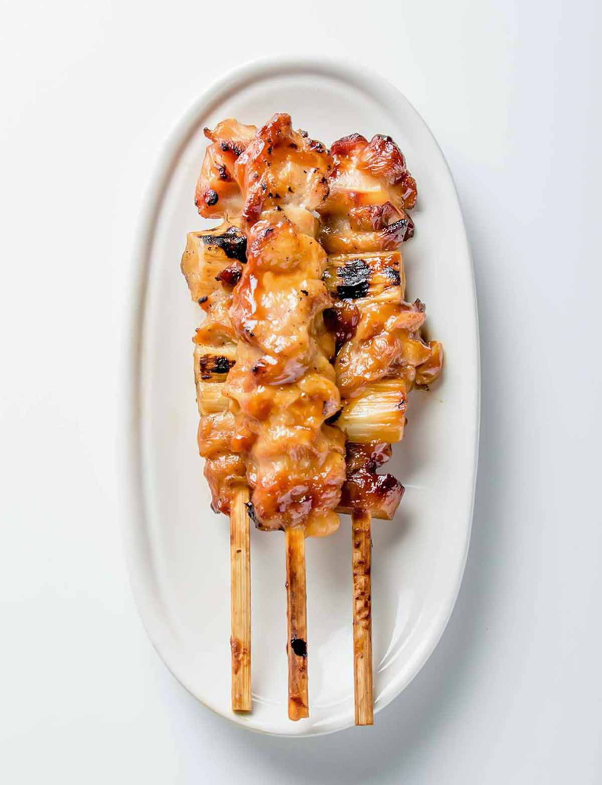 A white oval serving platter topped with three skewers of chicken yakitori with honey sauce.