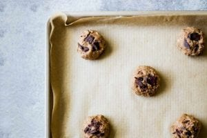 A parchment-lined rimmed baking sheet with balls of uncooked chocolate chip cookie dough in answer to the question 'why are my chocolate chip cookies flat?'.