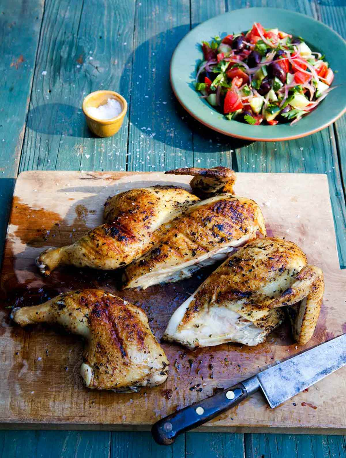 A wooden cutting board with a carved grilled Greek chicken and a knife resting beside it.