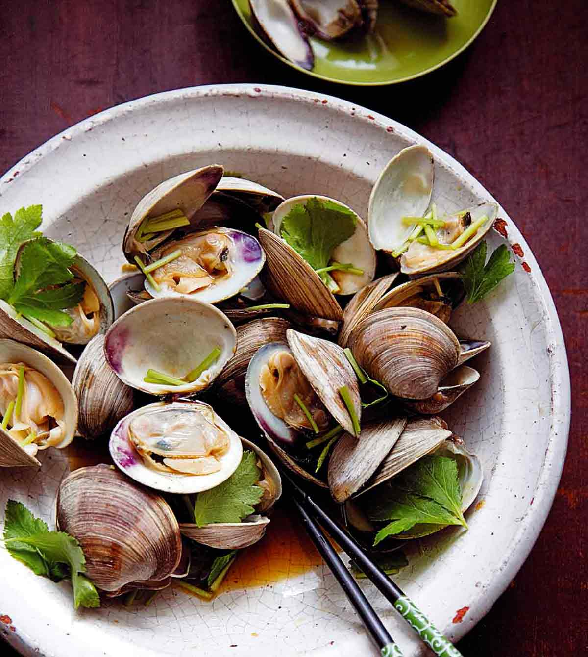 Bowl of grilled littleneck clams with soy sauce, cilantro leaves, and chopsticks