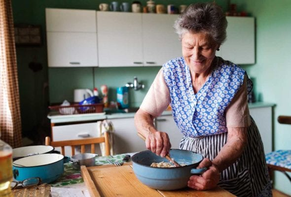 An elderly woman mixing bater in a enameled bowl to illustrate how cooking reminds you who you are.