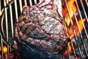 A grilled rib eye steak on a grill over open flame.