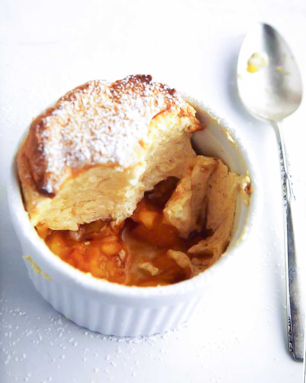 White dish of a sugar-dusted individual peach souffle; in the bottom are peach slices