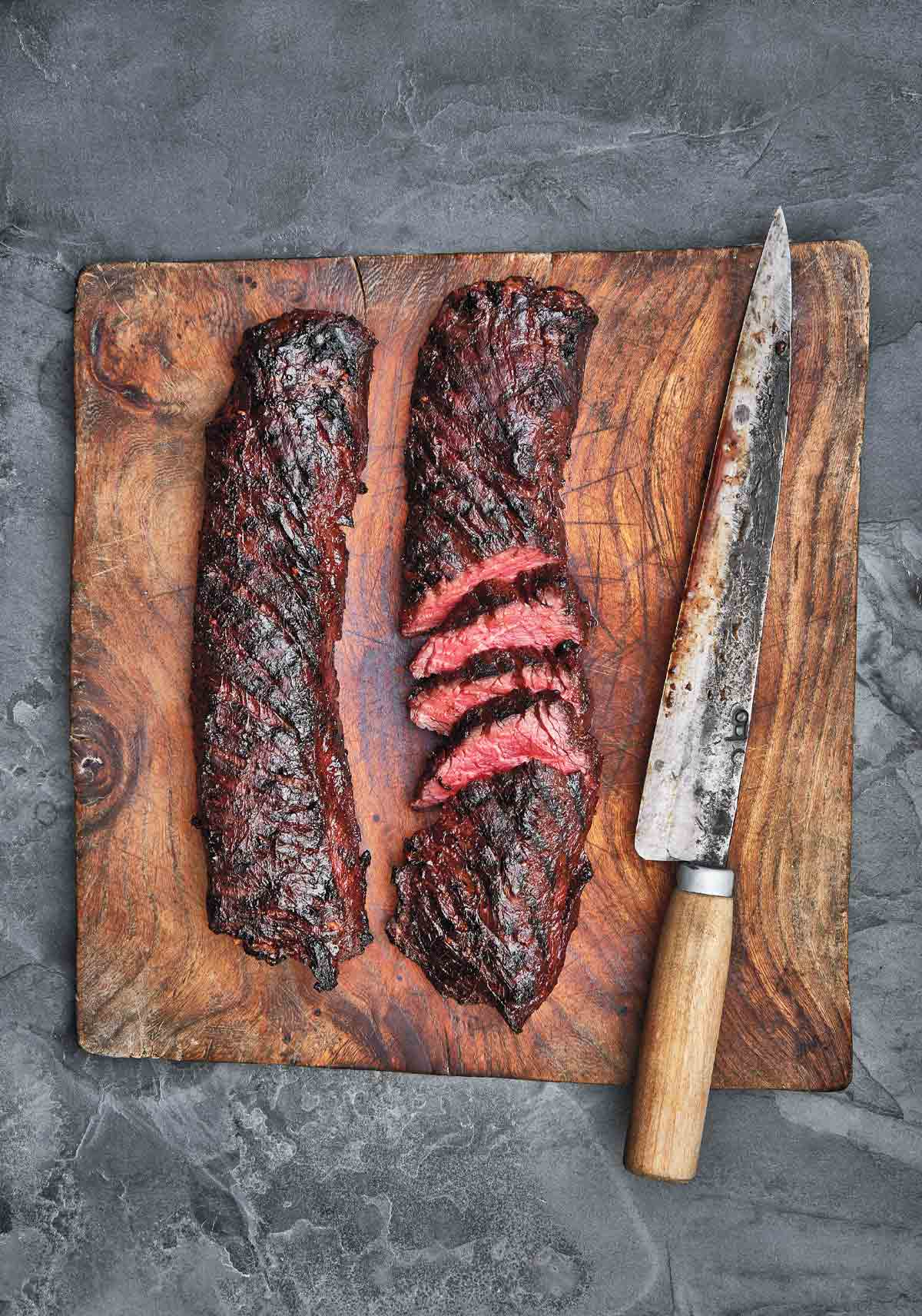 Two pieces of Korean style steak on a cutting board with a knife.