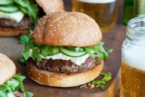 Three lamb burgers with arugula and feta on a wooden surface with two jars of beer beside them.