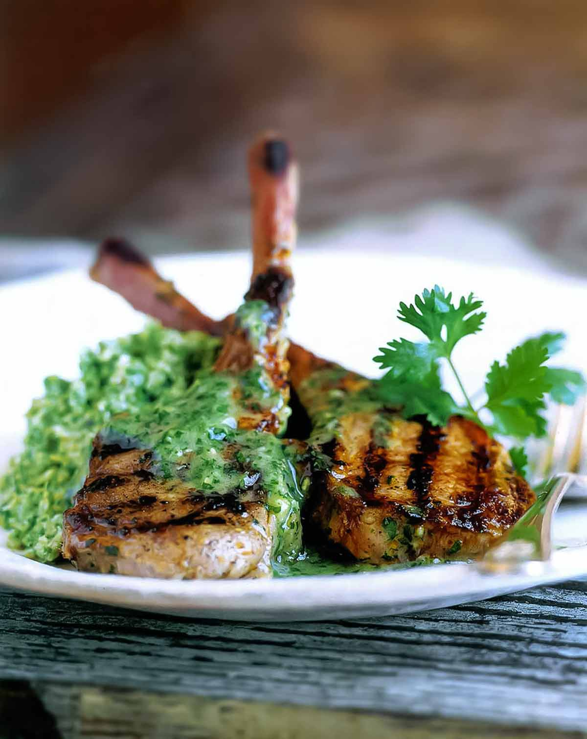 Two grilled lamb chops with cilantro-mint sauce on a white plate with a fork and a sprig of cilantro to garnish.
