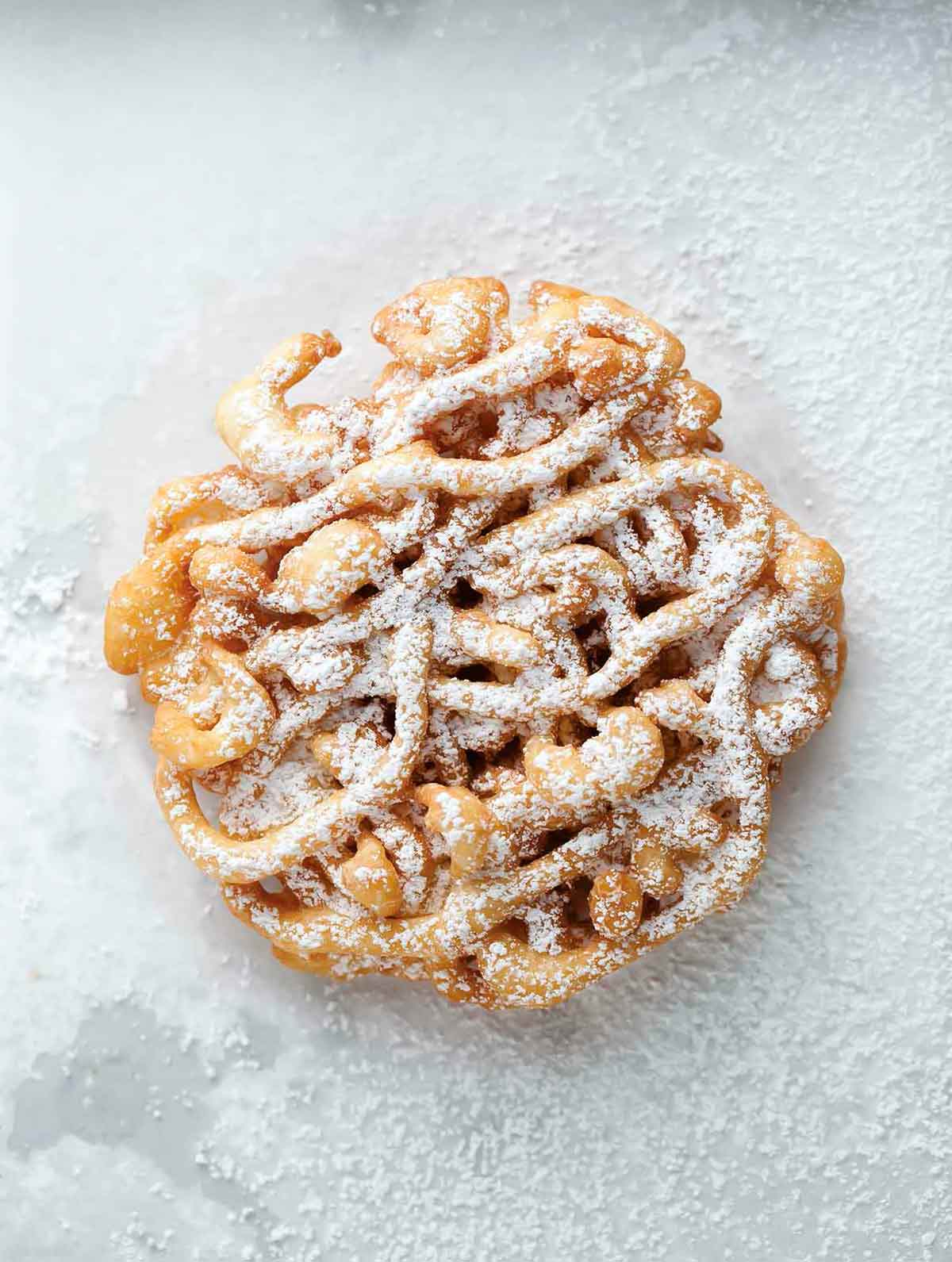 A mini funnel cake dusted with confectioners' sugar.