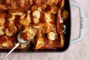 A Staub casserole dish filled with overnight French toast with caramel sauce and bananas and spoon resting in the dish.